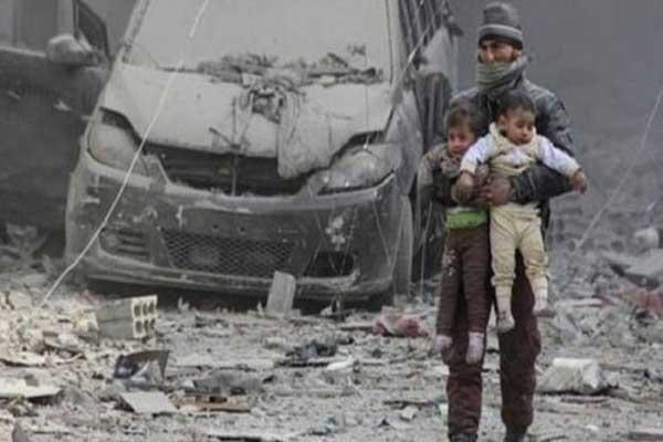 رجل يحمل طفلين في الغوطة الشرقية