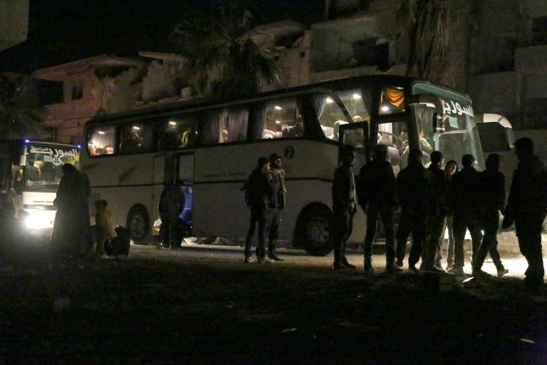 سوريون في حافلة في مدينة عربين يستعدون لمغادرة الغوطة الشرقية