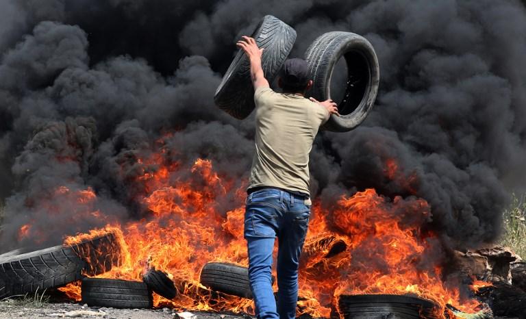 شاب فلسطيني يحرق الاطارات بالقرب من الحدود بين غزة واسرائيل
