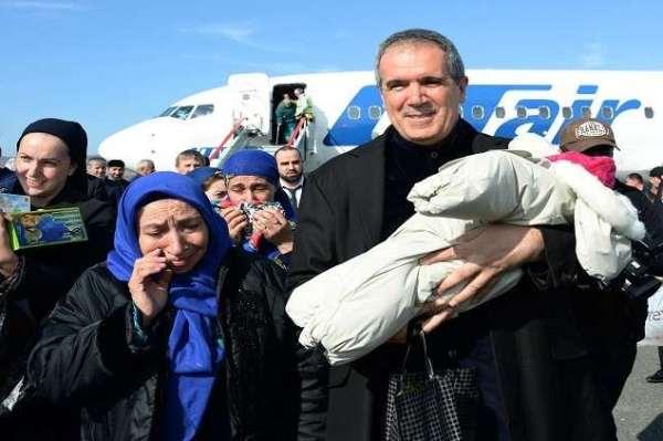 عضو مجلس الإتحاد الروسي يحمل أحد الأطفال الروس لدى وصولهم إلى روسيا