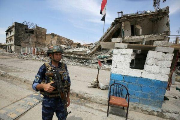 أحد عناصر الشرطة العراقية يقف عند حاجز أمني في الموصل القديمة