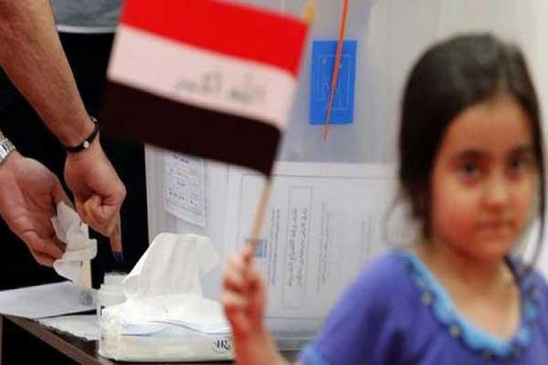 طفلة ترفع العلم العراقي في مركز انتخابي