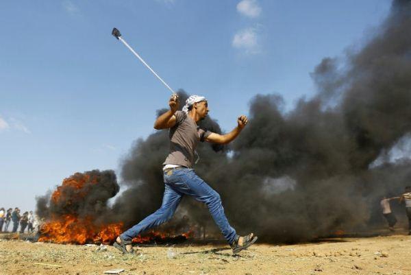شاب فلسطيني يلقي الحجارة خلال احتجاجات ومواجهات مع القوات الإسرائيلية