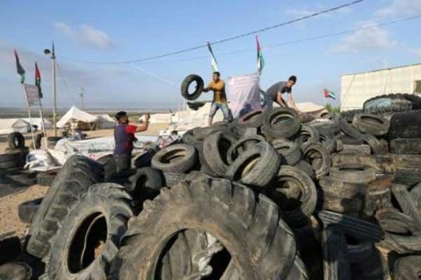 شاب يحضر الإطارات لحرقها مع استعداد الفلسطينيين لتظاهرة على حدود قطاع غزة مع إسرائيل في شرق جباليا في 14 مايو