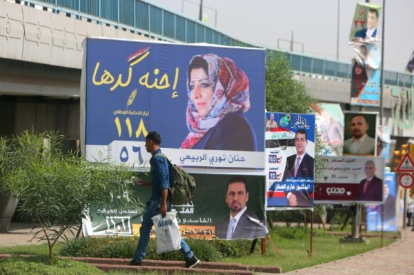 رجل يمر أمام لافتة انتخابية في بغداد