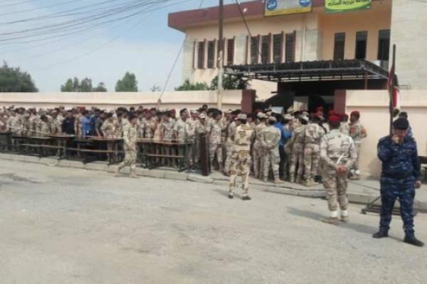 عسكريون عراقيون أمام إحدى محطات الانتخابات للادلاء بأصواتهم في الاقتراع الخاص