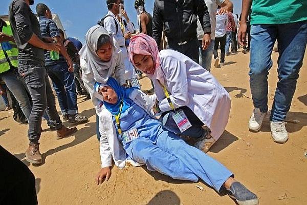المسعفة رزان النجار في يمين الصورة تحاول انقاذ إحدى زميلاتها