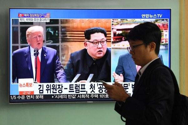 رجل يمر أمام شاشة تلفزيونية تظهر ترمب وكيم جونغ أون في سيول