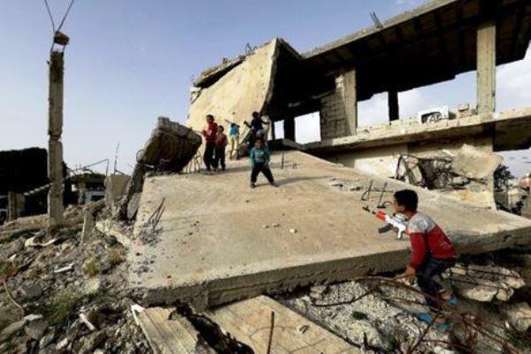 أطفال يلعبون فوق ما تبقى من منزل تعرض للهدم في معارك كوباني