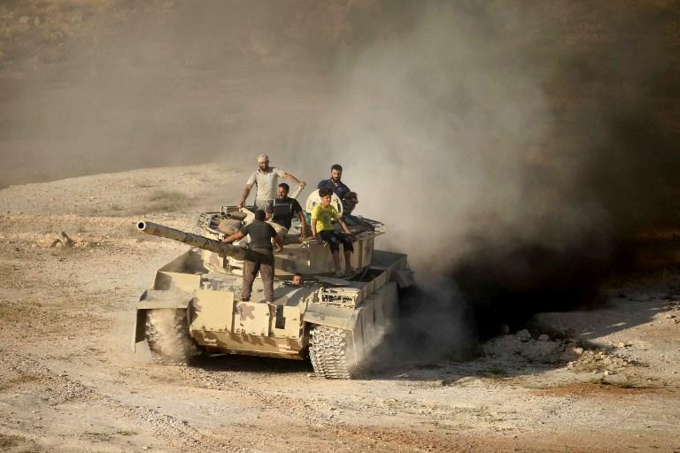 مقاتلون من المعارضة السورية على ظهر دبابة في ريف درعا