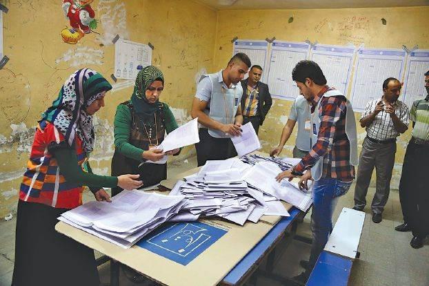 موظفو مفوضية الانتخابات العراقية يحصون اصوات الناخبين