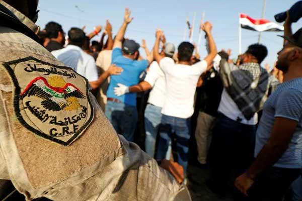 عنصر من قوات مكافحة الشغب العراقية يقف بالقرب من متظاهرين في مدينة البصرة بتاريخ 13 يوليو 2018