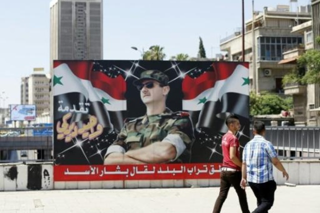 سوريان يمران امام صورة للرئيس السوري بشار الاسد في وسط العاصمة دمشق في 9 تموز/يوليو.