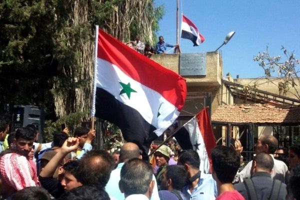سوريون يلوحون بالعلم بالقرب من مجلس بلدية طفس في ريف درعا
