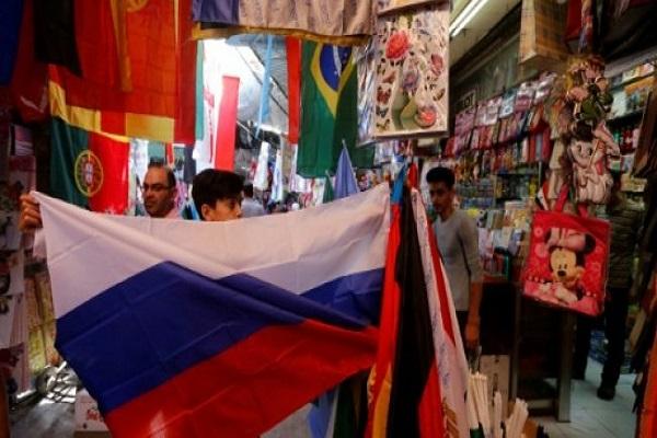 العلم الروسي بين مجموعة من أعلام المنتخبات المشاركة في كأس العالم في كرة القدم 2018، كما يبدو خارج متجر في دمشق القديمة