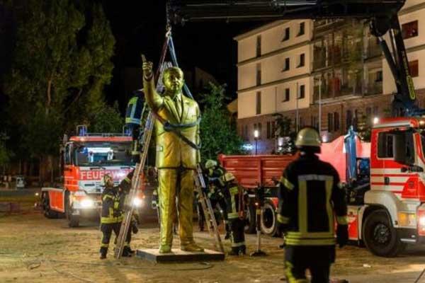 رجال إطفاء يزيلون تمثالًا لأردوغان من إحدى ساحات فيسبادن في غرب ألمانيا، الأربعاء 29 أغسطس 2018 بعد يومين على وضعه ضمن مهرجان بيينالي للفنون