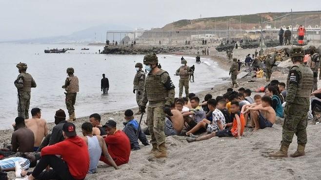 جنود اسبان يحيطون بعدد من المهاجرين غير الشرعيين (أ ف ب)