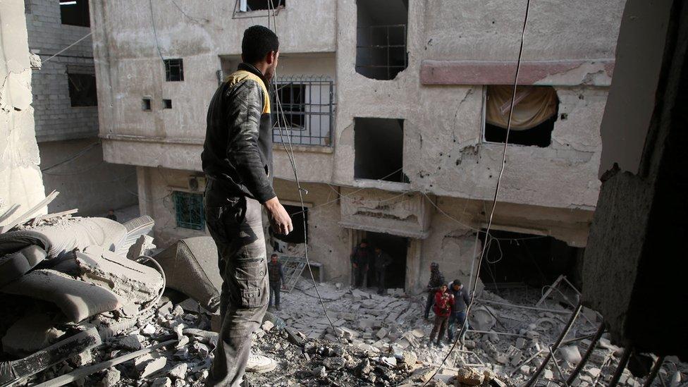أفراد الحماية المدنية أثناء جهود الإنقاذ بعد إحدى الغارات في الغوطة الشرقية
