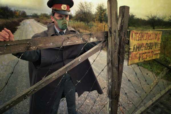 أحد أعضاء الميليشيا يضع علامة محظورة على سياج يقع داخل دائرة نصف قطرها تشيرنوبيل في حدود 30 كم في عام 1990