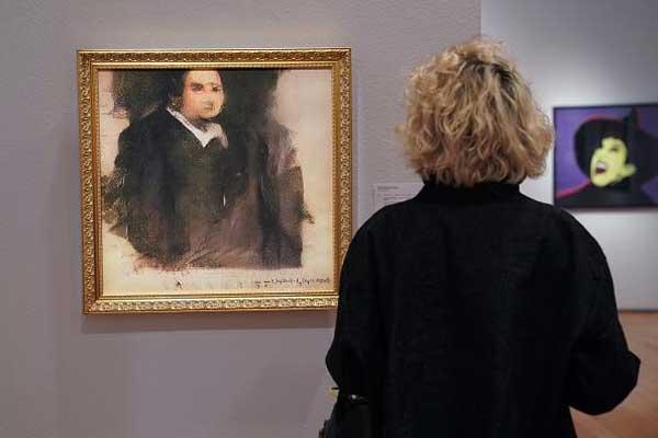 امرأة تنظر إلى عمل فني أُنجز بوساطة خوارزمية من قبل مجموعة فرنسية تسمى OBVIOUS والتي تنتج فنًا باستخدام الذكاء الاصطناعي