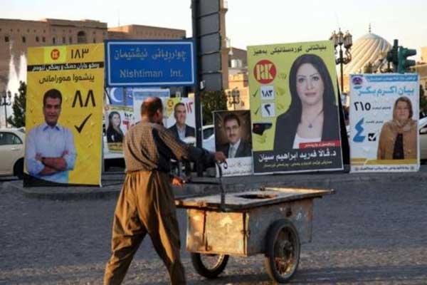 رجل يسير في أربيل أمام ملصقات مرشحين للانتخابات النيابية في كردستان العراق بتاريخ 26 سبتمبر 2018