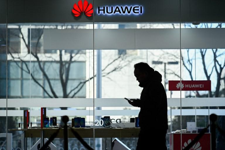 حريف ينظر إلى هواتف هواوي في متجر في بكين