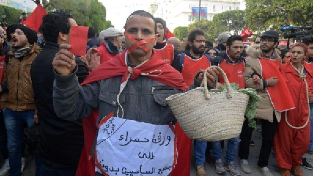رجل يحمل لافتة تندد بغلاء المعيشة خلال الاحتفالات بالذكرى الثامنة للثورة في تونس في 14 يناير 2019