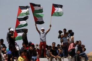 محتجون يرفعون الاعلام الفلسطينية على الحدود بين قطاع غزة وإسرائيل