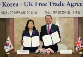 وزير التجارة الكورية الجنوبية يو ميونغ-هي مع وزير التجارة الدولية البريطاني ليام فوكس خلال حفل توقيع على اتفاق مبدئي للتجارة الحرة بين الطرفين في سيول بتاريخ 10 جزيران/يونيو 2019