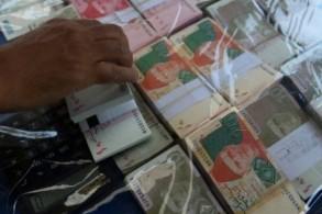 صراف عملة يرتب ورقات نقدية باكستانية في انتظار زبائن في شارع بكراتشي