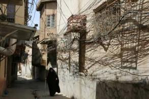 شبكة عشوائية من خطوط الكهرباء في شارع ضيق في حي باب السيف في بغداد في 11 يونيو 2019