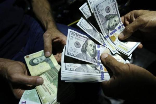 رجل يبدّل الريال الإيراني بالدولار الأميركي في متجر للصرافة في طهران