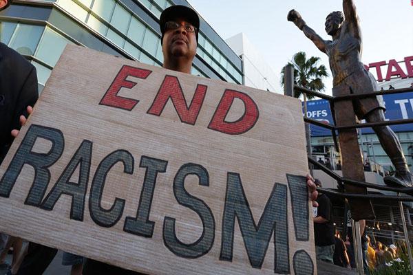 متظاهر يطالب بوقف العنصرية