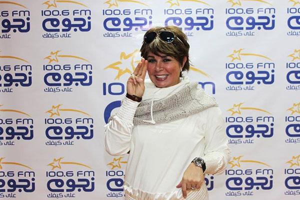 نجوى إبراهيم أمام الملصق الإعلاني لإذاعة نجوم FM