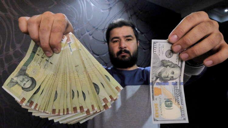 صراف ايراني بين دولارات وريالات ايرانية