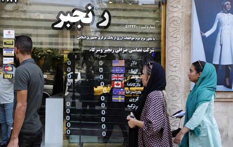 مواطنون إيرانيون أمام محول للعملات في طهران