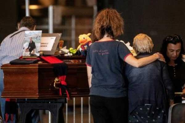 أقارب ضحايا انهيار الجسر في جنوى يصلّون أمام نعش وضع في مركز ستقام فيه مراسم الجنازة للضحايا السبت 17 أغسطس 2018