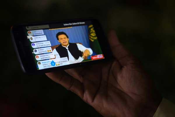 باكستاني يتابع عبر هاتفه المحمول أول خطاب لرئيس الوزراء الجديد عمران خان في كراتشي بتاريخ 19 أغسطس 2018