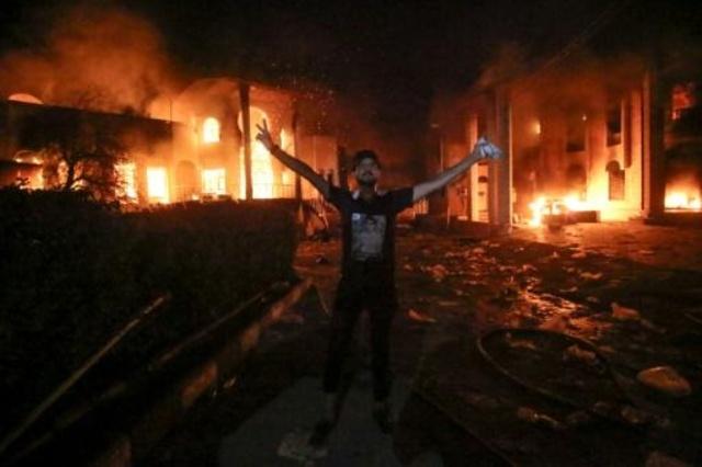 عراقي يرفع شارة النصر أمام القنصلية الإيرانية بعد إحراقها