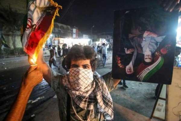 متظاهر عراقي يحمل علمًا إيرانيًا وشخص آخر يضرم النار فيه خلال احتجاجات في البصرة في 7 سبتمبر 2018