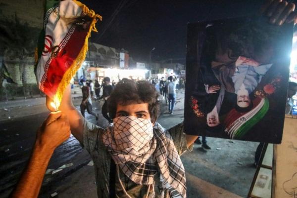 متظاهر عراقي يحمل علما إيرانيا وشخص آخر يضرم النار فيه خلال احتجاجات البصرة