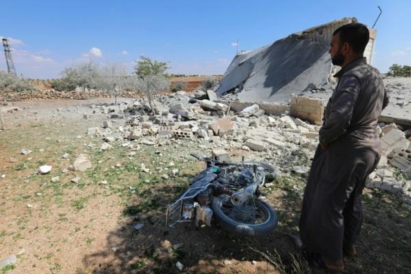 سوري يقف قرب منزل مدمر بعد غارات لقوات النظام على بلدة المنطار في إدلب