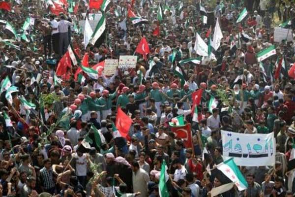 سوريون يرفعون أعلام المعارضة والأعلام التركية خلال تظاهرة ضد الحكومة في معرّة النعمان في شمال محافظة إدلب بتاريخ 21 سبتمبر 2018