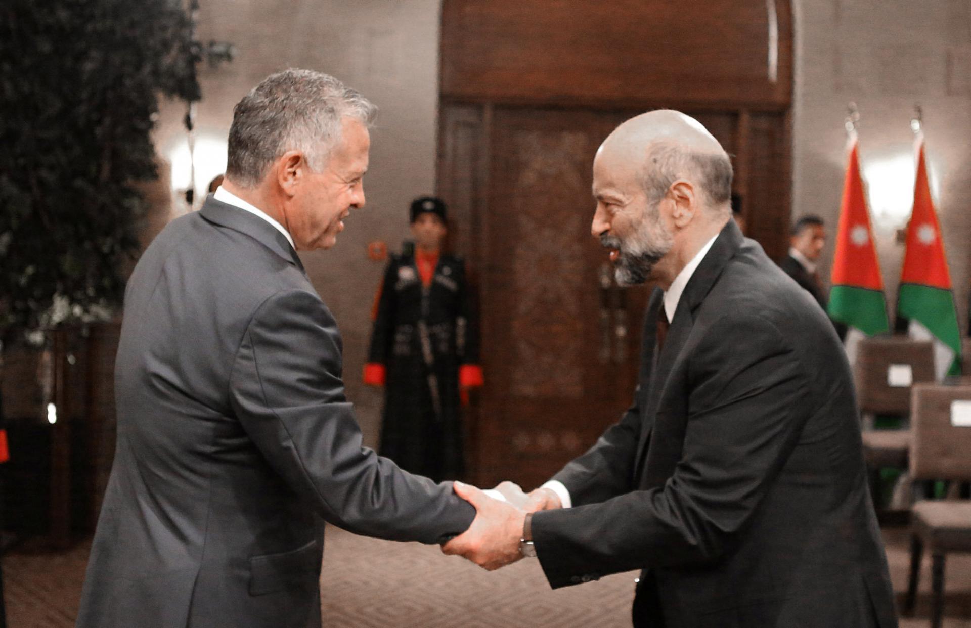 عاهل الأردن مصافحا رئيس حكومته عمر الرزاز