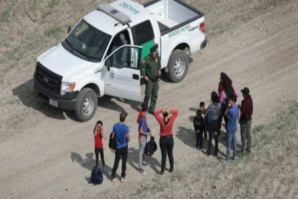 طالبو لجوء يتحدثون مع دورية أميركية بعد عبور الحدود مع المكسيك بتاريخ 7 نوفمبر 2018 في ميشن في ولاية تكساس