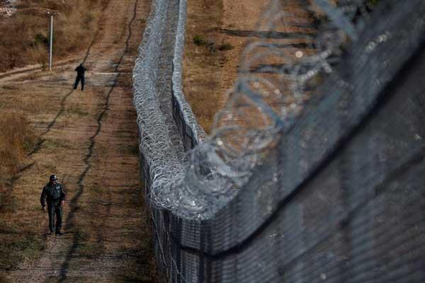 ضابط بلغاري يقوم بدورية أمنية أمام سياج من الأسلاك الشائكة على الحدود التركية