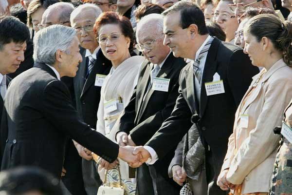 الإمبراطور الياباني آكيهيتو (يسار) مصافحًا رئيس مجلس إدارة تحالف نيسان-رينو-ميتسوبيشي إلى جانب زوجته ريتا (يمين) خلال حفل في طوكيو عام 2004 - أرشيفية