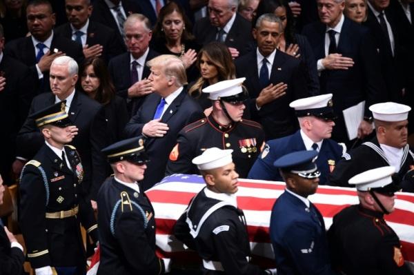 دونالد ترمب وزوجته ميلانيا الى باراك أاوباما ونائب الرئيس مايك بنس عند مرور نعش جورج بوش الاب في واشنطن