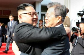 صورة التقطت في 26 مايو 2018 يظهر فيها الرئيس الكوري الجنوبي مون جاي إن والزعيم الكوري الشمالي كيم جونغ أون يتعانقان بعد قمتهما الثانية في الشمال في قرية بانمونجوم في المنطقة المنزوعة السلاح