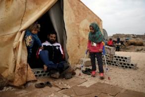 مايا مرعي الى جانب والدها المعوق امام خيمة عائلتها في احد المخيمات في شمال غرب سوريا في التاسع من ديسمبر 2018